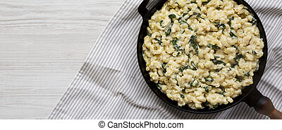 Homemade Spinach Mac and Cheese in a cast-iron pan on a white wooden table, top view. Flat lay, overhead, from above. Space for text.