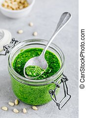 Homemade spinach pesto sauce in glass jar with parmesan cheese and olive oil