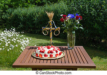 Homemade strawberry cake on decorated table in garden