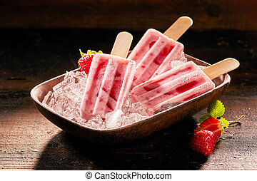 Homemade strawberry popsicles with fresh fruit displayed in a dish on ice over a rustic wooden table for a healthy summer treat rich in vitamins