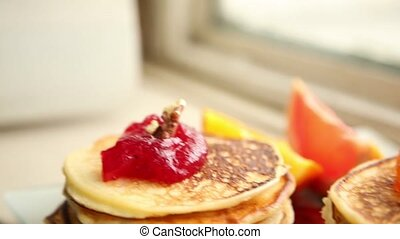 Homemade sweet pancakes with fruit jam, sour cream on a...