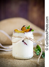 Homemade sweet yogurt with slices of ripe plums in a glass