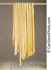 tagliatelle on a wooden stick to dry