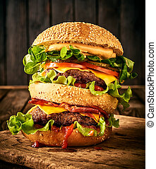 Homemade tasty double burger with beef, salad, bacon, tomatoes and cheese on wooden background