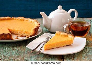 Homemade tasty pumpkin pie and black tea on shabby wooden table