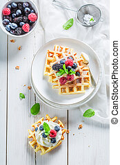 Homemade tasty waffles with berry fruits and mint leaves