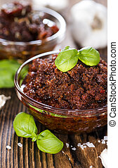 Homemade Tomato Pesto in a small bowl (on wooden background)