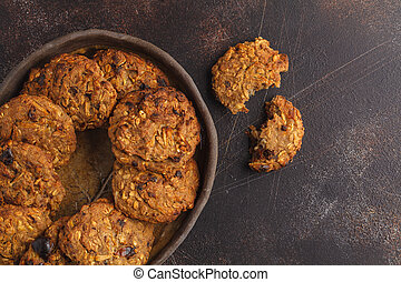 Homemade vegan oatmeal cookies with raisins, pecans and dates. Healthy vegetarian food concept. Dark rusty background, copy space, top view.