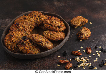 Homemade vegan oatmeal cookies with raisins, pecans and dates. Healthy vegetarian food concept. Dark rusty background