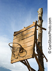 Homemade vintage backboard of wood planks with rusted nails and rusted basket for basketball play in a poor rural Western village.