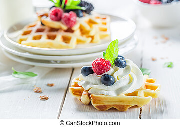 Homemade waffles with berry fruits and mint leaves
