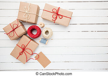 Homemade wrapped rustic brown paper packages on white wooden surface