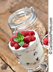 Homemade yogurt with oatmeal and fresh raspberries in a glass and mint leaves, full glass of oatmeals in background