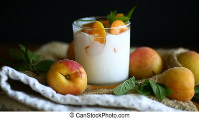homemade yogurt with ripe apricots on wooden background