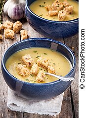 homemade zucchini cream soup with croutons in blue bowls
