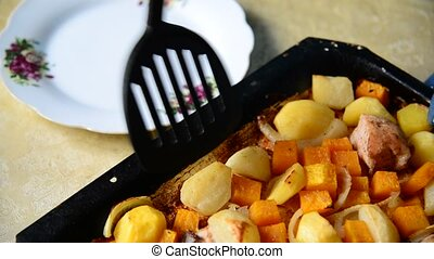 Homemaker puts in plate Baked potatoes with chicken and pumpkin