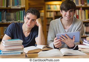 homens jovens, olhar, de, estudar, em, biblioteca