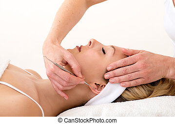 Homeopath using ear acupuncture techniques.