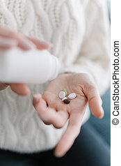 Homeopathic medicine. Female hands open pills of vitamins and probiotics in the palm of your hand, close-up. The concept of natural and harmless drugs