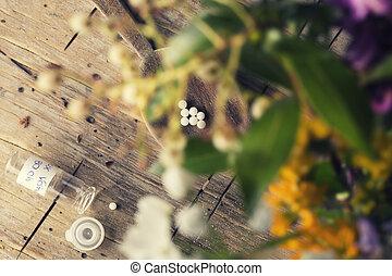 Homeopathy globules between blur flowers