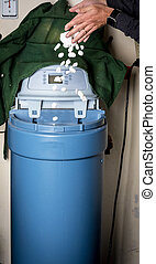 Homeowner adds salt to a water softener - Hands pour salk...