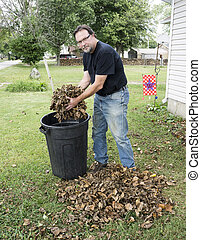 Homeowner Scooping Leaves And Putting Them In A Barrel -...