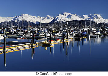 Winter view of boat marina in Homer Alaska . Snow capped mountains in background