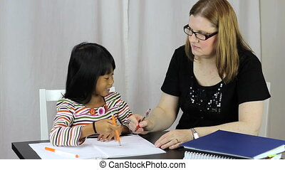 A pretty woman teaching her cute Asian daughter during a homeschool lesson at home.