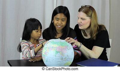 Homeschool Teacher Uses Globe - A pretty housewife uses a...