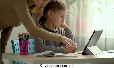 Homeschooling for children. Son and daughter use a laptop for education. Mom helps with homework. Stay home concept.