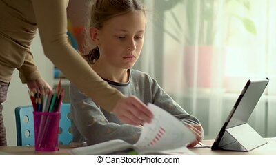 Homeschooling for children. Son and daughter use a laptop for education. Mom helps with lessons. Girl is upset and dont want to do homework. Stay home concept.