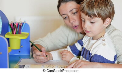 Mother helping her kid to make drawings