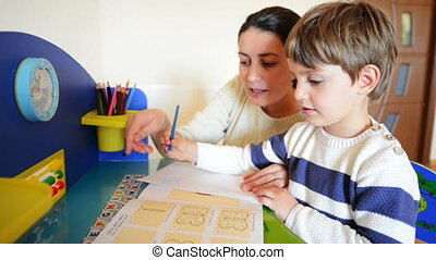 Homeschooling - Mother helping her kid to make drawings