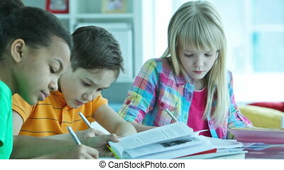 Homework doers - Children doing homework together at home or...