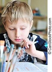 homework - left-handed boy doing a home task at home