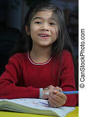 Homework time - Six year old girl doing her homework at...