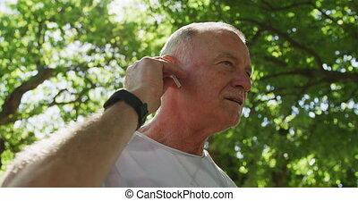 homme, écouteurs, utilisation, parc, personne agee, sans fil