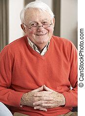 homme aîné, délassant, dans chaise, chez soi