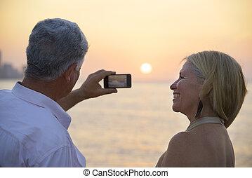 homme aîné, et, femme utilise téléphone portable, prendre,...