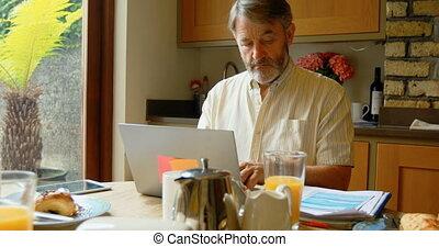 homme aîné, ordinateur portable, utilisation, dîner, 4k, table