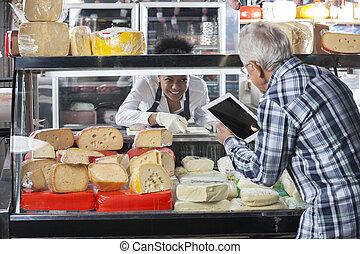 homme aîné, utilisation, tablette numérique, dans, fromage, magasin