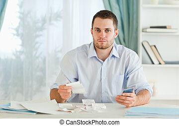 homme affaires, à, calculatrice, vérification, factures