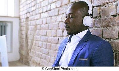 homme affaires, écouteurs, laptop., fonctionnement, africaine