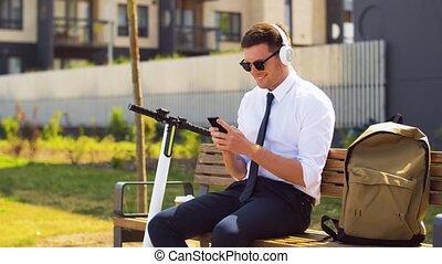 homme affaires, cellphone, écouteurs, scooter