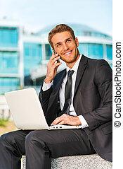 homme affaires, fonctionnement, outdoors., beau, jeune homme, dans, formalwear, travailler, ordinateur portable, et, conversation, sur, les, téléphone portable, quoique, séance, dehors, et, contre, structure bâtiment