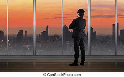 homme affaires tient, dans, bâtiment bureau, regarder, cityscape, horizon, lumière nuit