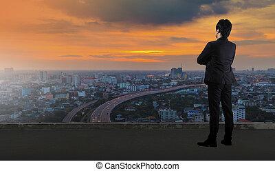 homme affaires tient, sur, toit, et, regarder, cityscape, horizon, lumière nuit