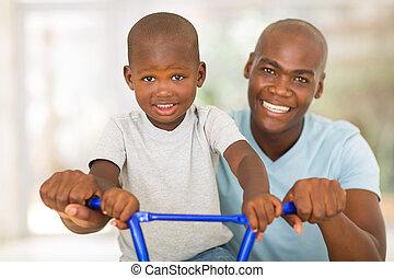 homme africain, portion, fils, monter, a, vélo