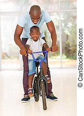 homme africain, portion, sien, fils, monter, a, vélo