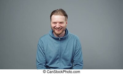 homme, blonds, rire, heureux, vidéo, sweatshirt, bleu